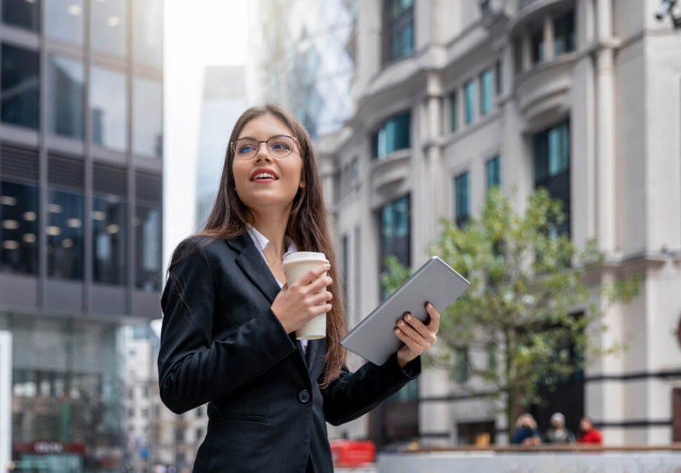 Moça jovem executiva segura copo de café e tablet na rua
