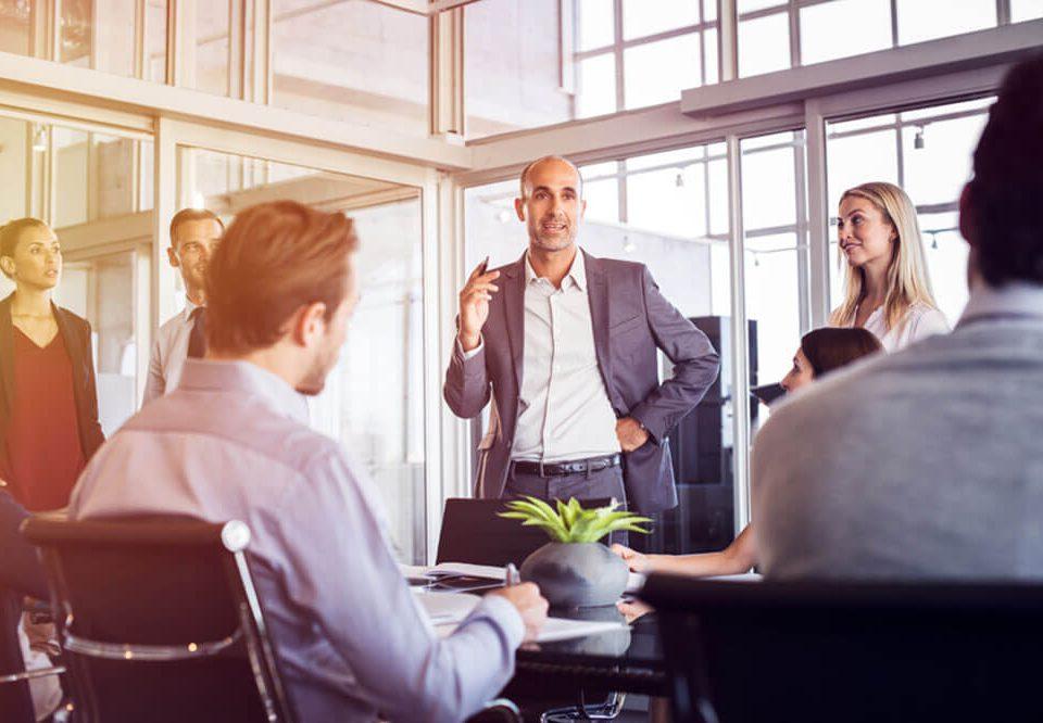 Homem fala em pé em reunião para grupo de profissionais