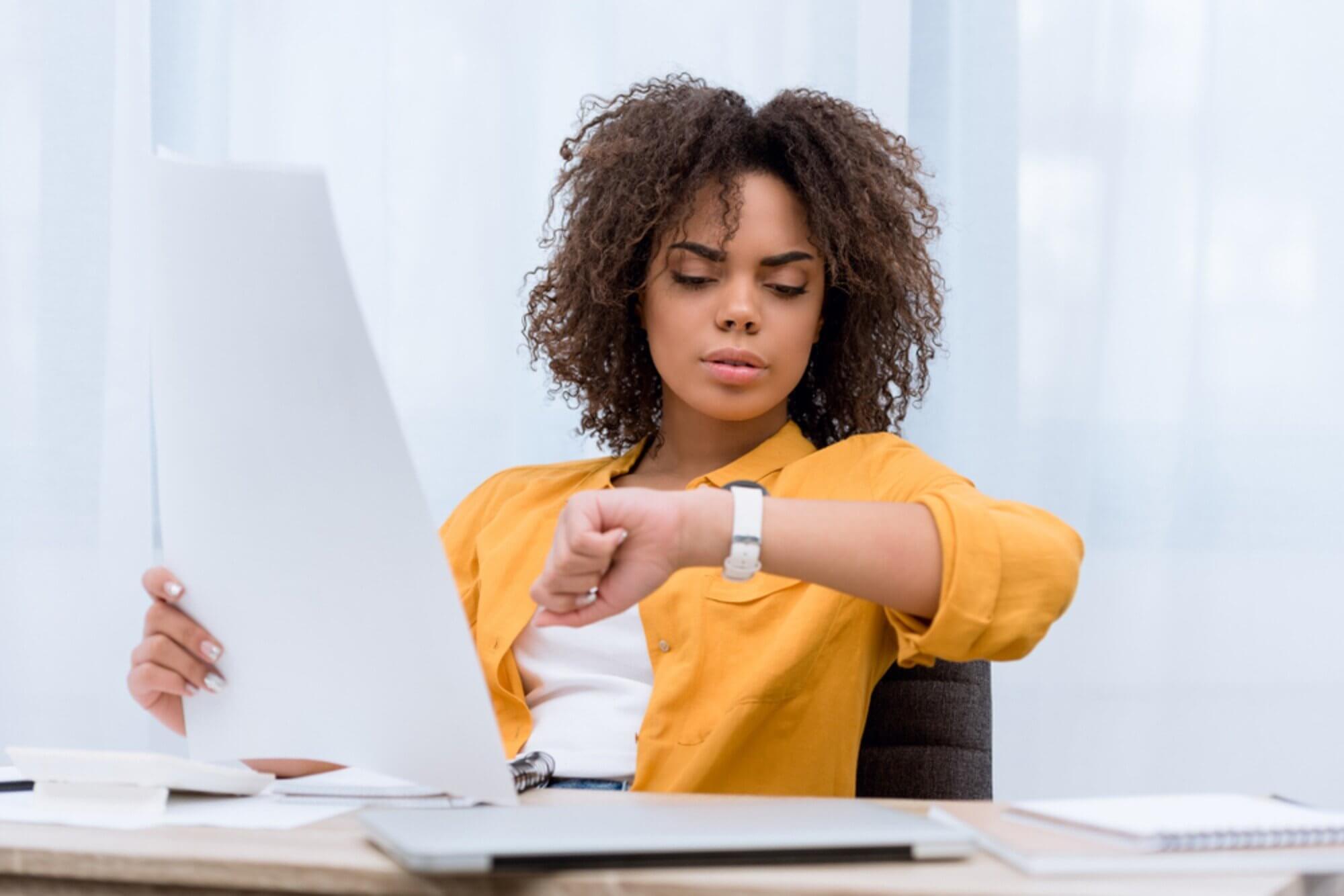 Moça olha para o relógio preocupada enquanto trabalha em relatórios