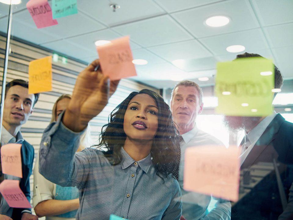 Grupo de pessoas em reunião discutem ideias utilizando cartões e post-it